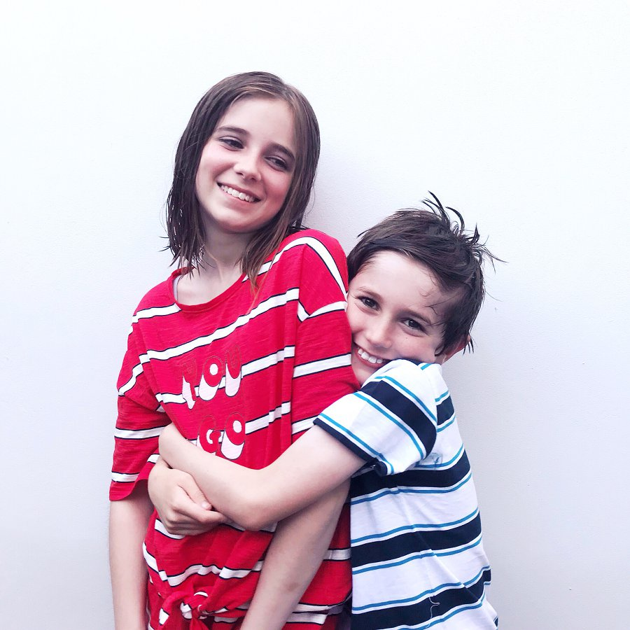 Brother and sister in pyjamas cuddling and smiling