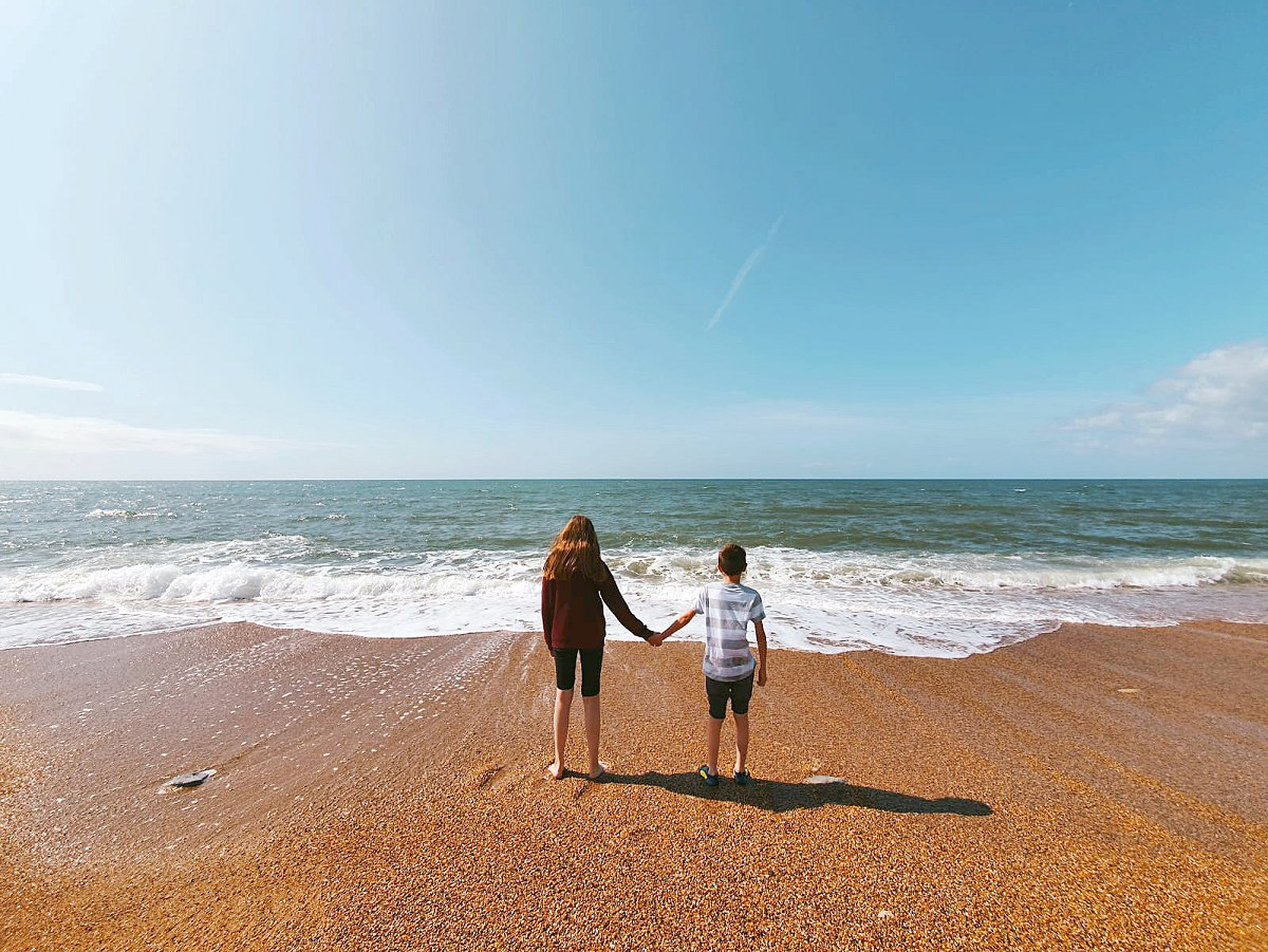 two children holding hands on a beach