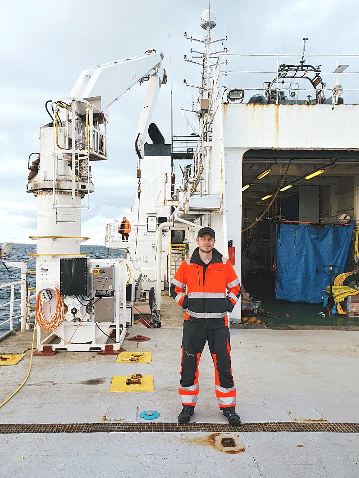 Man in high-vis workwear on a large boat