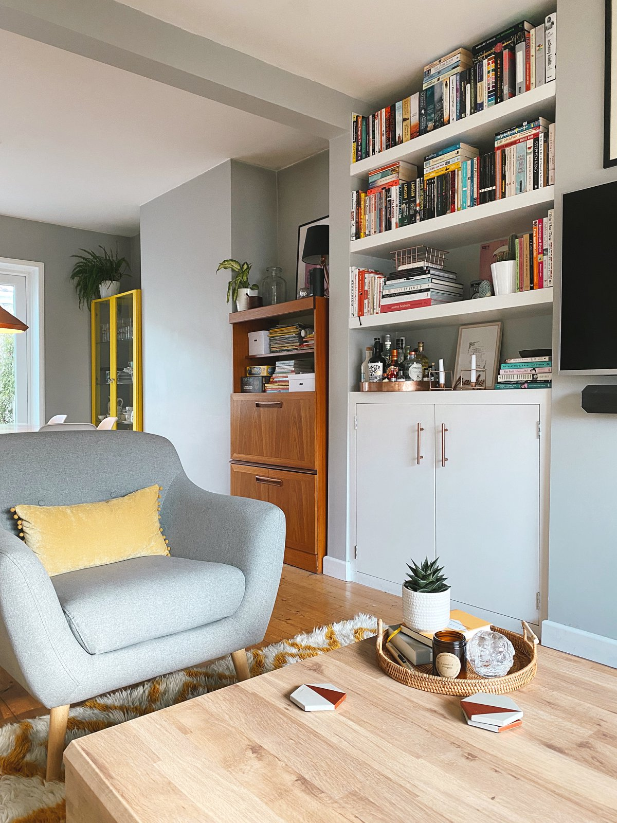 Love Audrey living/dining room grey chair with yellow pompom cushion